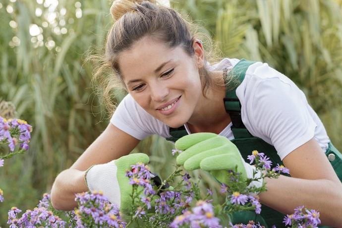 kobieta dbająca o kwiaty w okół ogrodu