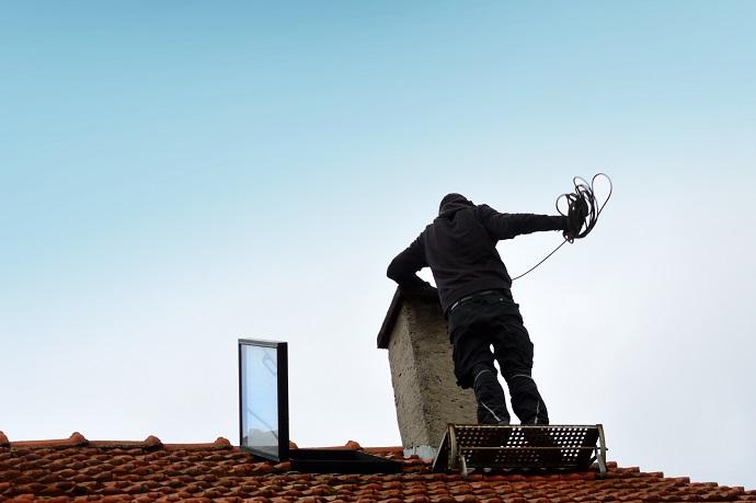 Kominiarz na dachu robiący przgląd kominowy