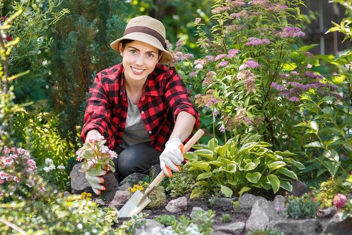 zadowolona kobieta z pięknych kwiatów w ogrodzie